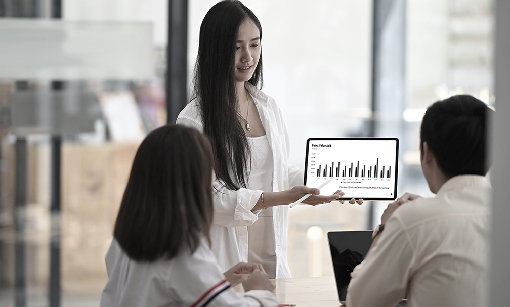 Woman showing two other people data on laptop